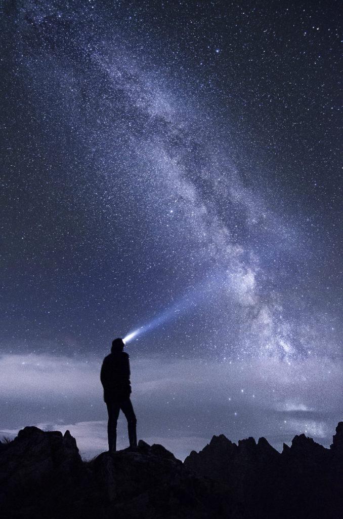 Mensch der mit Licht in den Sternenhimmel sieht.